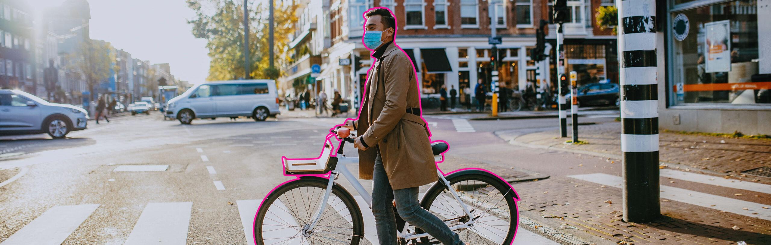 Man walking a bike across a crosswalk